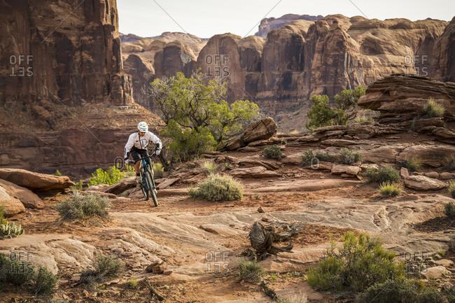 A man mountain biking on the Hymasa trail, Moab, Utah