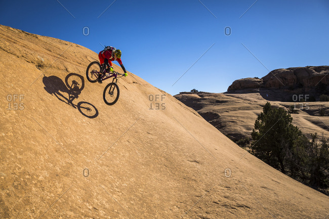 A man mountain biking on the slickrock trail, Moab, Utah