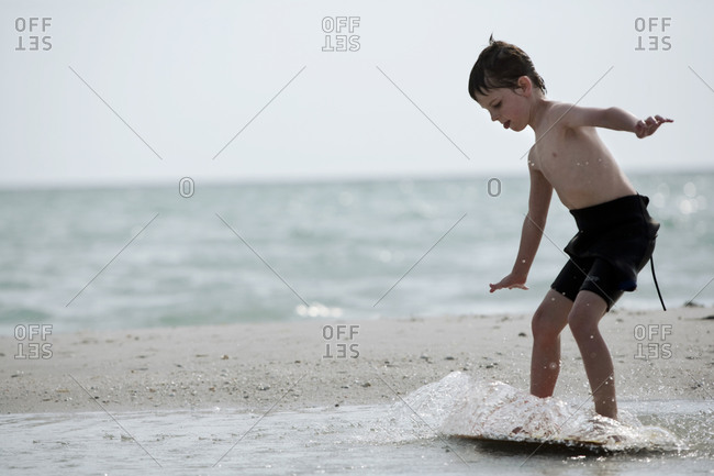 A young boy in a wetsuit surfs on his skim board at the shore