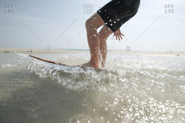 An action shot of a boy on a skim board at the shoreline