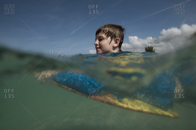 A split level underwater shot of a young boy on a boogie board