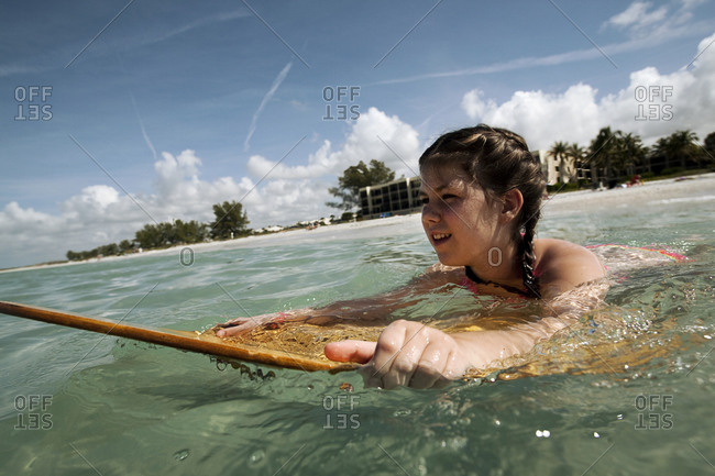 A young girl boogie boards in the ocean with blue skies and clouds in the background