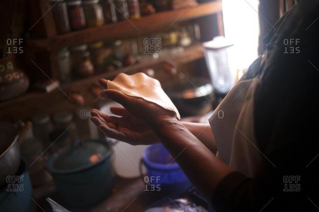 A woman makes organic corn tortillas