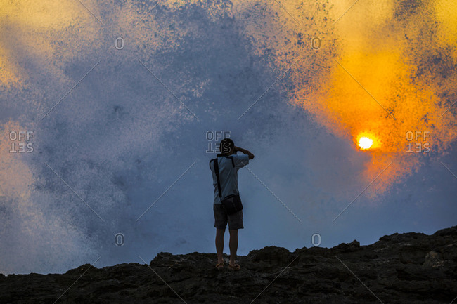 Silhouette of Young Photographer at Ocean Coast at sunset time