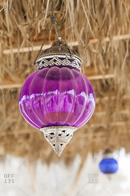 Glass lanterns hang from the thatched roof of Cafe Ezuz in Ezuz, Israel