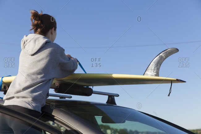 Woman taking surf board off car roof