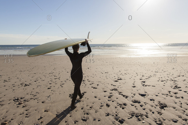 Girl with surf board on beach