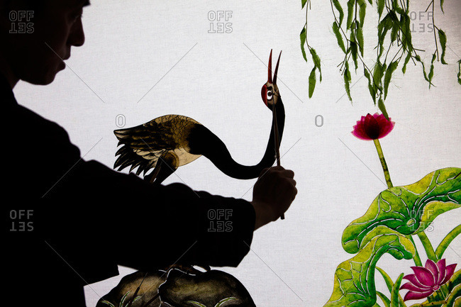 Man painting a bird on a screen