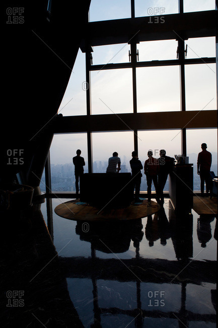 Silhouettes of people standing at the window of a high rise