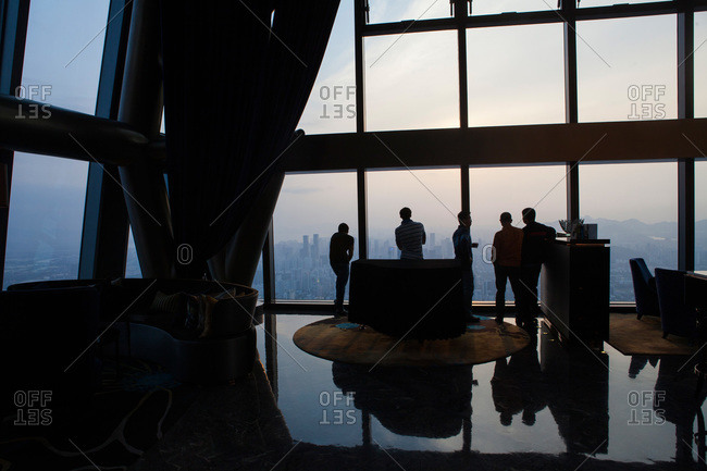 Silhouettes of men standing at the window of a skyscraper