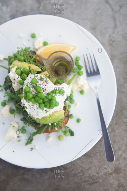 Toast topped with eggs, avocado, and peas