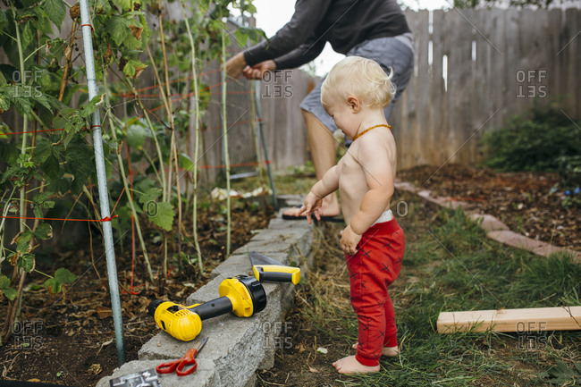 Little boy crying while his father works in the garden