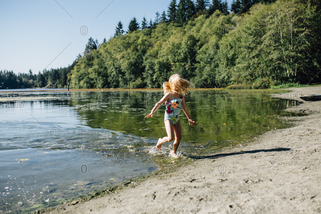 Little girl running through water at a lakeshore