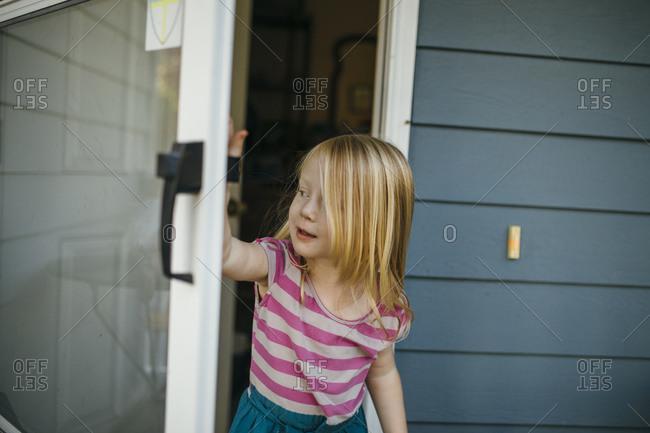 Little girl peering through an open storm door