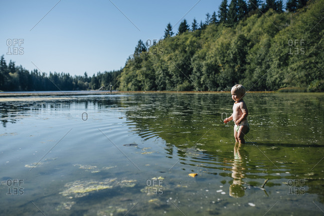Toddler boy standing in a shallow lake
