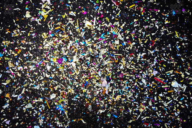 Colorful paper confetti scattered over black surface