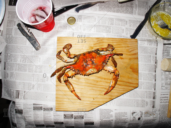 Overhead view of fresh crab on newspaper-covered table
