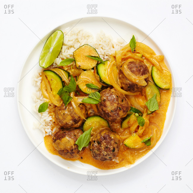 Overhead view of red curry with meatballs and zucchini on rice