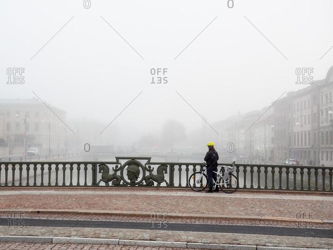 Bicyclist standing on a bridge in the fog in Gothenburg, Sweden
