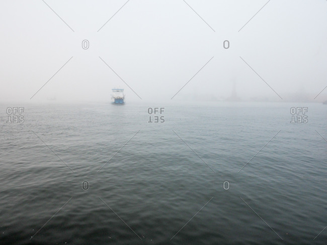 Distant boat across foggy waters in Gothenburg, Sweden