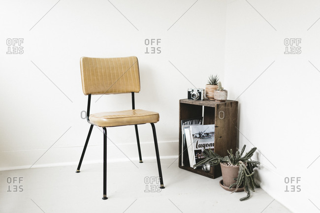 Vintage chair in corner next to crate with books and plants