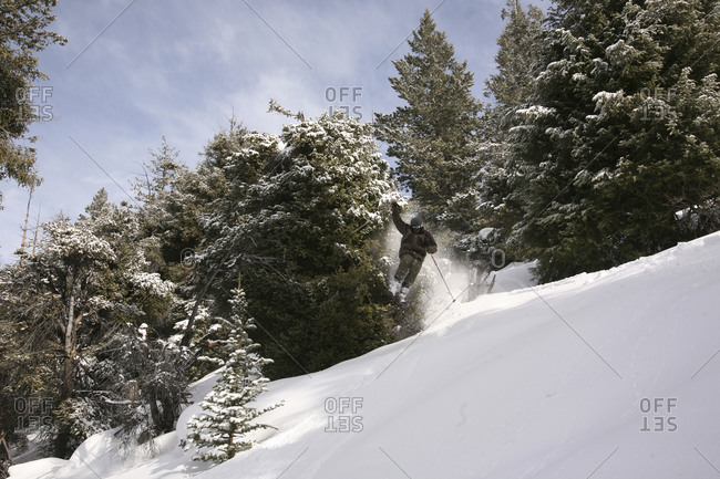 Skier landing a jump on a snowy slope