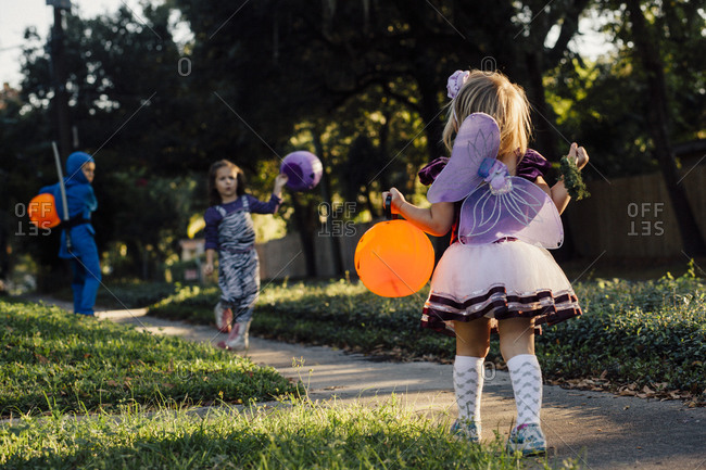 Kids in Halloween costumes playing on a sidewalk