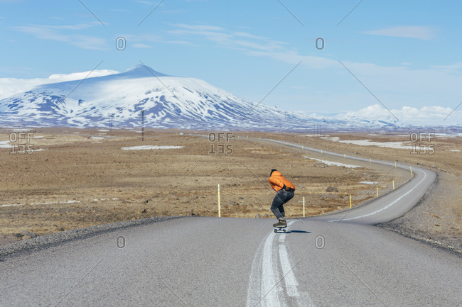 Young man skateboarding on a highway near a volcano