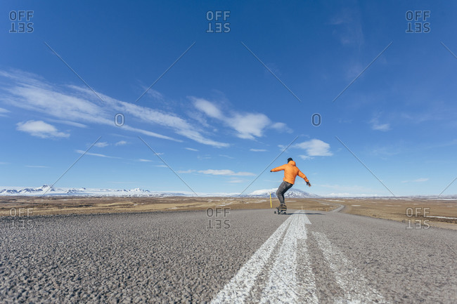 Young man skateboarding on an empty highway