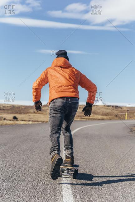 Skateboarder on an empty highway in Iceland