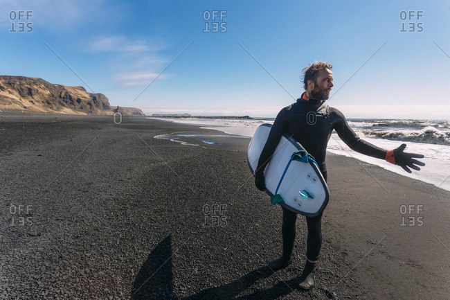Surfer in wetsuit carrying his surf board waving his hand