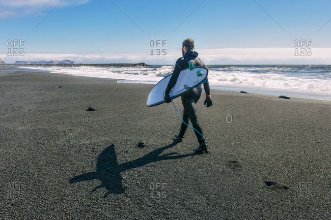 Surfer in wetsuit carrying his surf board as he walks along the beach