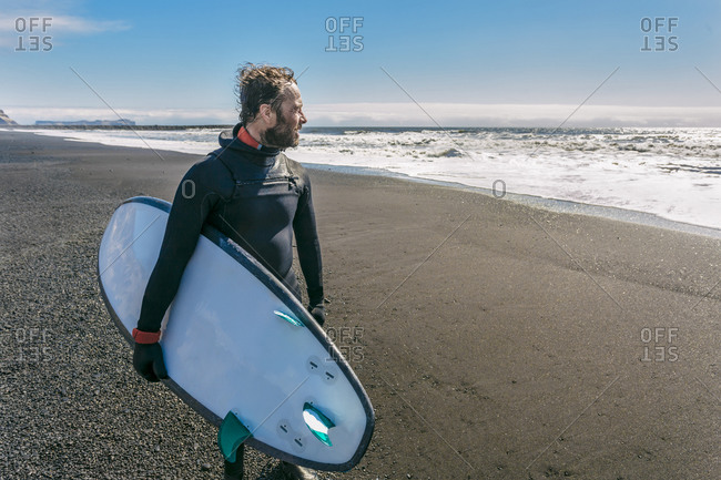Surfer in wetsuit carrying his surf board looking at the waves