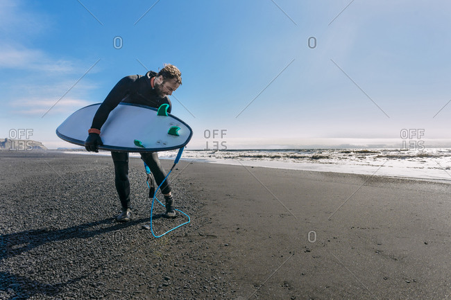Surfer in wetsuit reaching down to untie his board leash