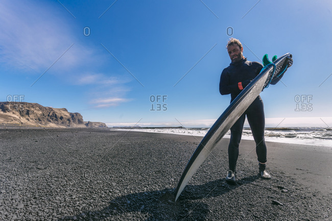 Surfer in wetsuit standing his board up on the beach