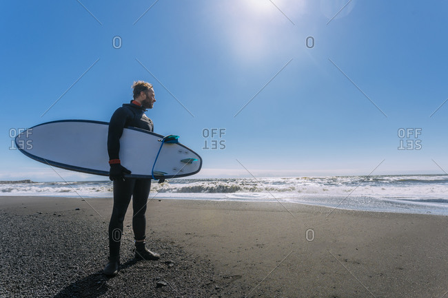 Surfer standing in wetsuit holding his surf board looking at the ocean