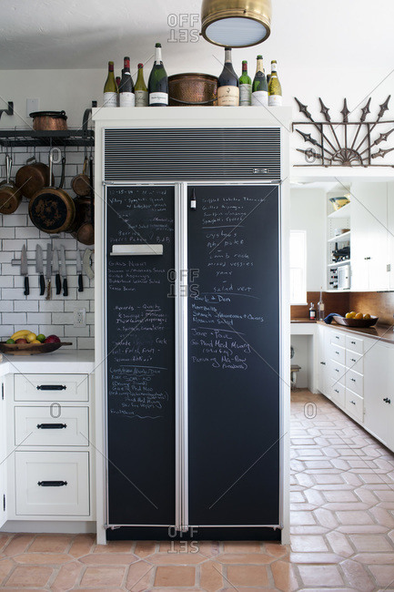 Refrigerator With Chalkboard Painted Doors And Wine Bottle On Top