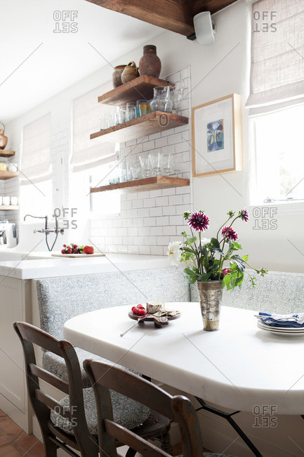 White dining table in kitchen with vase filled with red and white asters