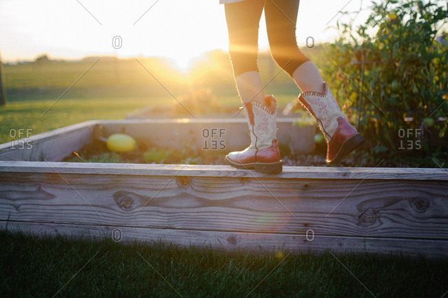 Girl wearing red cowboy boots standing on edge of raised garden at sunset
