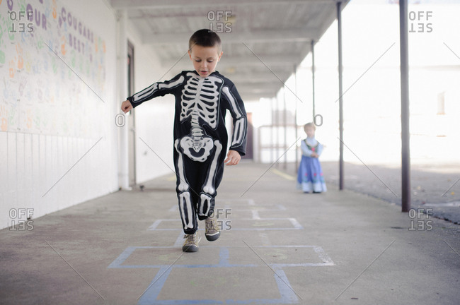 Little boy playing hopscotch dressed as skeleton for Halloween