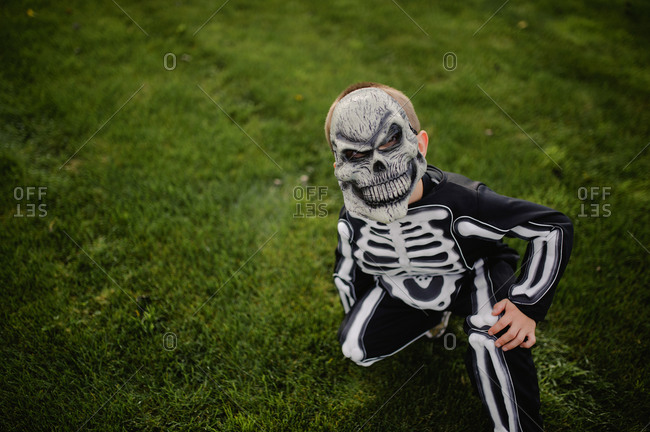 Little boy dressed in skeleton costume with scary mask
