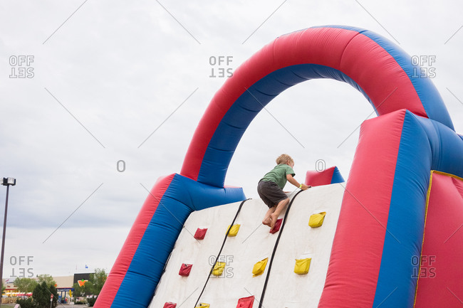 Boy climbing to top of inflatable climbing wall