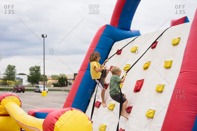 Boys climbing up inflatable climbing wall