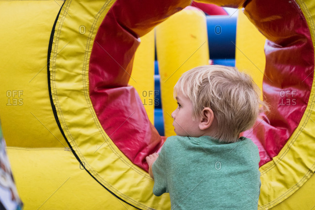 Boy standing by inflatable bounce house