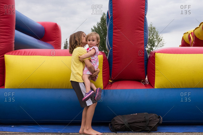 Boy holding sister by inflatable bounce house
