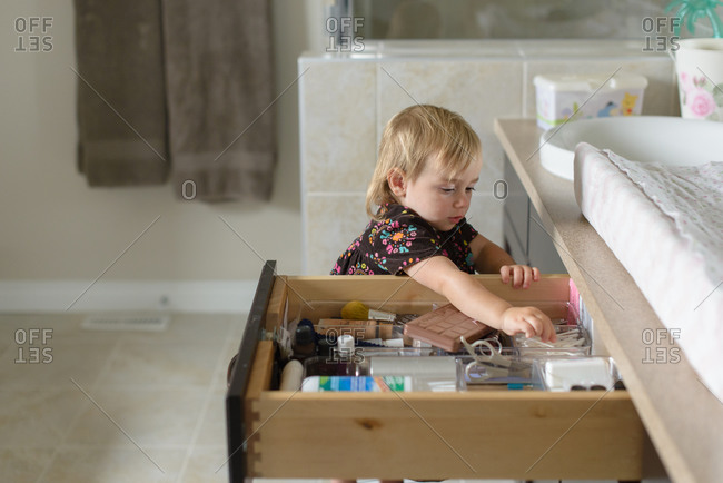 Little girl grabbing cotton swab from drawer