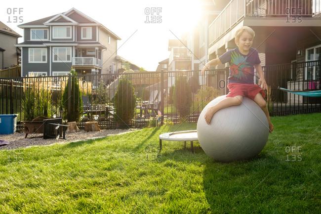 Boy in backyard on an exercise ball
