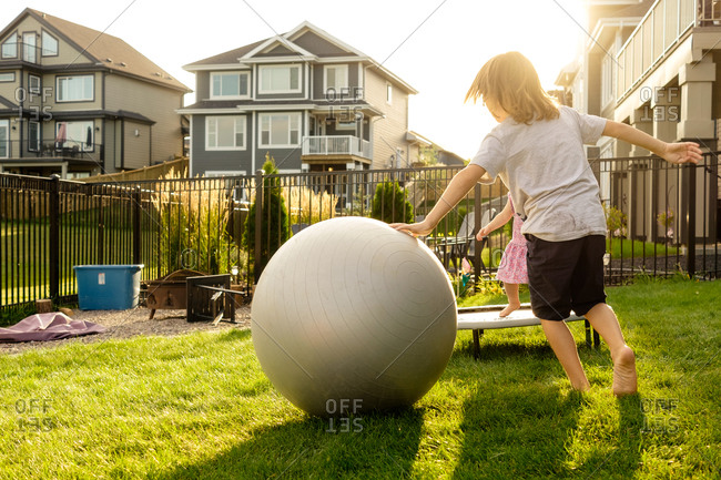 Kids playing with exercise ball and trampoline