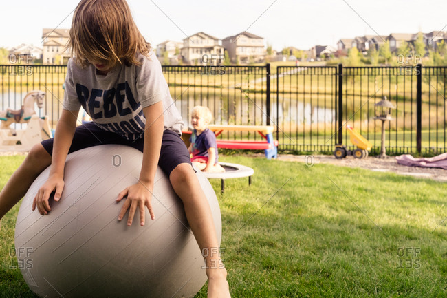 Kids sitting on exercise ball and trampoline