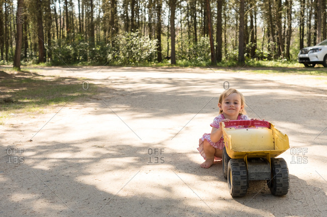 Little girl on dirt road with toy dump truck